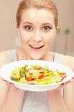 Den unga kvinnan lagar mat sallad Arkivbild