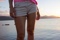 Den unga kvinnan lägger benen på ryggen closeupen Royaltyfria Bilder