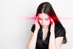 Den unga kvinnan lider från en huvudvärk Ståenden av en flicka med smärtar punkter på hennes huvud arkivfoton