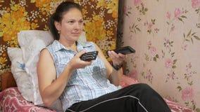 Den unga kvinnan ligger hemma på soffan med lag från TV:N Ser uppmärksamt på skärmen stock video