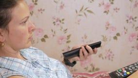 Den unga kvinnan ligger hemma på soffan med lag från TV:N Ser uppmärksamt på skärmen arkivfilmer