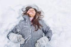 Den unga kvinnan ligger i en snödriva och skratt royaltyfri foto