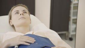 Den unga kvinnan ligger i förväntan av massagetillvägagångssättanti--cellulite som är pressotherapy på kliniken inomhus lager videofilmer