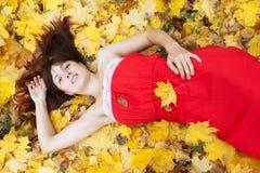 Den unga kvinnan ligger i höstpark Royaltyfria Foton