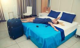 Den unga kvinnan ligger och har en vila på sängen i hotellrummet royaltyfria foton