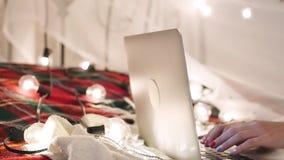 Den unga kvinnan ligger på en säng med en bärbar dator på en girlandbakgrund, video pratstund, gör ett online-köp lager videofilmer