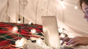 Den unga kvinnan ligger på en säng med en bärbar dator på en girlandbakgrund, video pratstund, gör ett online-köp arkivfilmer