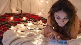 Den unga kvinnan ligger på en säng med en minnestavla på en bakgrund av en girland, gör ett online-köp lager videofilmer