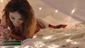 Den unga kvinnan ligger på en säng med en minnestavla på en bakgrund av en girland, gör ett online-köp stock video
