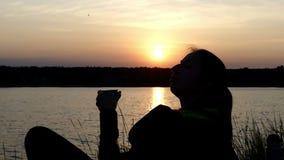 Den unga kvinnan ligger på en sjöbank, dricker te och skrattar lager videofilmer