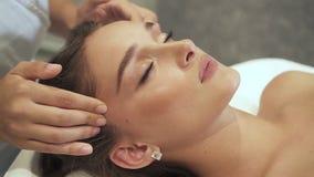 Den unga kvinnan ligger på massagetabellen och får att trycka på för hälsovård arkivfilmer