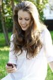 Den unga kvinnan läser sms Arkivfoto