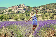 Den unga kvinnan lyftte henne händer upp i lavendel royaltyfri bild