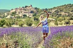 Den unga kvinnan lyftte henne händer upp i lavendel royaltyfri foto