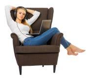 Den unga kvinnan lyssnar musik med hörlurar arkivbilder