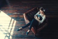 Den unga kvinnan lyssnar till musik inomhus royaltyfri foto