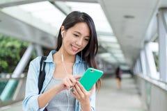 Den unga kvinnan lyssnar till musik på mobiltelefonen arkivfoto