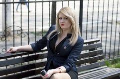 Den unga kvinnan lyssnar till musik parkerar in Royaltyfria Foton