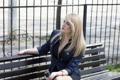 Den unga kvinnan lyssnar till musik parkerar in, på en bänk Arkivfoto