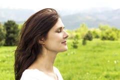 Den unga kvinnan med ögon stängde att andas djupt ny luft i bergen Arkivfoton