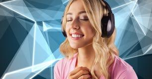 Den unga kvinnan med ögon stängde att lyssna till musik på hörlurar Royaltyfri Fotografi
