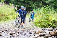 Den unga kvinnan med barn på cyklar vadar strömmen royaltyfri fotografi