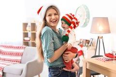 Den unga kvinnan med behandla som ett barn i julhattar Royaltyfri Foto