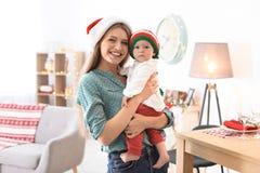 Den unga kvinnan med behandla som ett barn i julhattar Arkivbilder