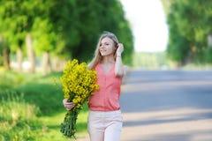 Den unga kvinnan med buketten av gula färger går på landsvägen royaltyfria foton