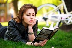 Den unga kvinnan med cykelläseboken i stad parkerar på gräs arkivbild