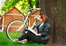 Den unga kvinnan med cykelläseboken i stad parkerar på gräset royaltyfria bilder