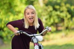 Den unga kvinnan med cykeln i gräsplan parkerar fotografering för bildbyråer