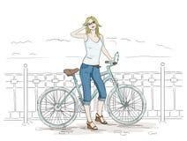 Den unga kvinnan med cykeln skissar blå nätt flickajeans Arkivbilder
