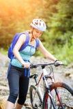 Den unga kvinnan med cykeln vadar berglilla viken Arkivbild