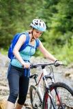 Den unga kvinnan med cykeln vadar berglilla viken Royaltyfria Bilder
