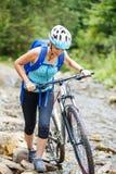 Den unga kvinnan med cykeln vadar berglilla viken Royaltyfri Fotografi