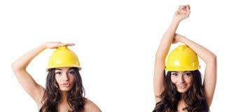 Den unga kvinnan med den gula hårda hatten på vit Royaltyfri Foto