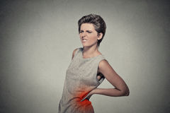 Den unga kvinnan med den tillbaka ryggvärken smärtar tillbaka färgat i rött Arkivfoton