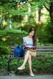 Den unga kvinnan med en anteckningsbok i händer som sitter på, parkerar bänken royaltyfria foton