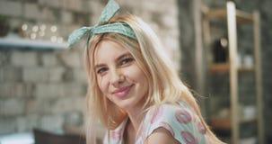 Den unga kvinnan med en attraktiv framsidastående för blont hår som ser rak till kameran och hon, ler gulligt har hänglsen stock video