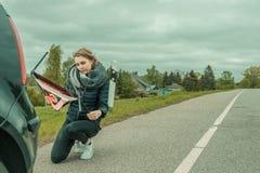 Den unga kvinnan med en bilsammanbrott försöker att montera den varnande triangeln arkivbild