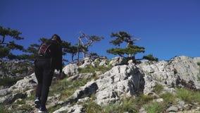 Den unga kvinnan med en ryggsäck klättrar överst av berget lager videofilmer