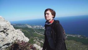 Den unga kvinnan med en ryggsäck klättrar överst av berget ovanför havet lager videofilmer