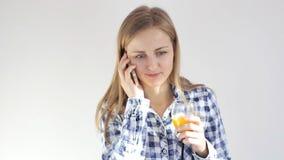 Den unga kvinnan med ett exponeringsglas av fruktsaft talar på mobiltelefonen lager videofilmer