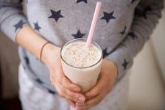 Den unga kvinnan med ett stort exponeringsglas av den sunda smoothien tjänade som med ett sugrör och havre Händer som rymmer milk arkivbilder