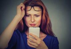Den unga kvinnan med exponeringsglas som har problem som ser mobiltelefonen, har visionproblem Royaltyfria Foton