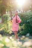 Den unga kvinnan med flätade trådar i en sommar parkerar i rosa kläder i sommar utomhus Fotografering för Bildbyråer