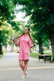 Den unga kvinnan med flätade trådar i en sommar parkerar i rosa kläder i sommar utomhus Royaltyfri Foto
