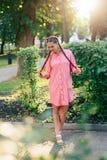 Den unga kvinnan med flätade trådar i en sommar parkerar i rosa kläder i sommar utomhus Royaltyfria Foton