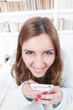 Den unga kvinnan med galet framsidauttryck försöker att förarga insidi arkivfoto